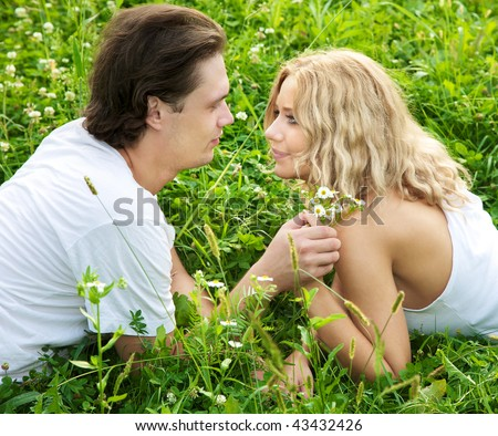 The young loving couple looking against each other on a green blossoming meadow