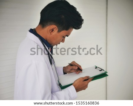 the Young male medical Doctor physician Reading diagnosis The patient information chart  in his Office clinic Hospital University Bangkok Thailand