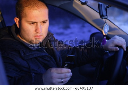 The young man at the wheel talks by a mobile phone
