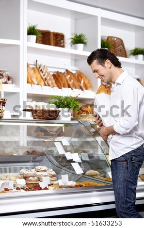 The young man buys bread in shop