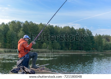 The young man catching fish on the lake from an aged pier. #721180048