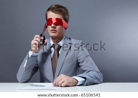 The young man cut the ribbon that closes his eyes - stock photo