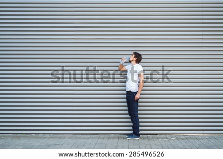 The young man drinks water on a metallic background