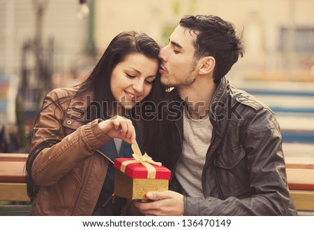 The young man gives a gift to a young girl in the cafe and they are kissing.
