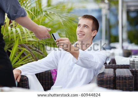 The young man gives the waiter a credit card - stock photo