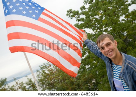 The young man holds in hands the USA flag on a background of a sea gulf.