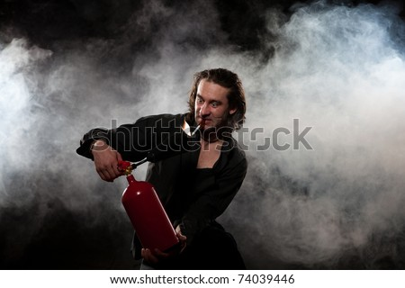 The young man in a black shirt extinguishes a burning cigarette. The man uses the red fire extinguisher. White smoke on a dark background.