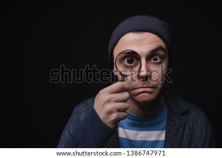 The young man in casual clothes with a magnifier. The guy is looking for opportunities. Private detective. I look at all. Explores. Looks to the future #1386747971