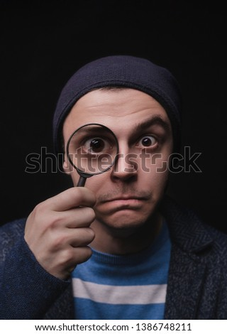 The young man in casual clothes with a magnifier. The guy is looking for opportunities. Private detective. I look at all. Explores. Looks to the future #1386748211