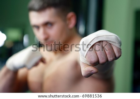 The young man is engaged in boxing in sports hall and beats on a pear