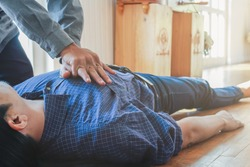 The young man is helping his unconscious friend and stop breathing on the floor with CPR, as he had previously trained to rescue the unconscious and stopped breathing. concept of saving lives with CPR