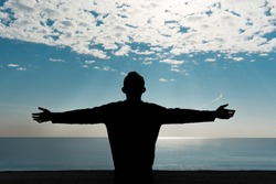 The young man is looking at the sea with his hands raised. The praying man spread his arms. Silhouette of a man raise his hands up to sunset panoramic view.