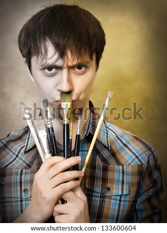 The young man jokes with art brushes