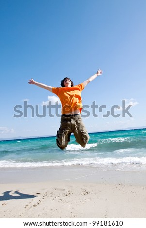 The young man jumps on sand at the sea