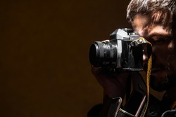 The young man photographs a retro old camera. Dark background.