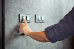 The young man's hand turned off the light switch