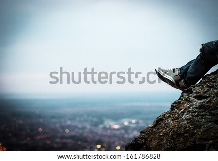 The young man sits on a rock above the city in the sunset