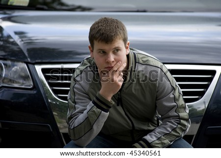 The young man sits with a thoughtful face near the car