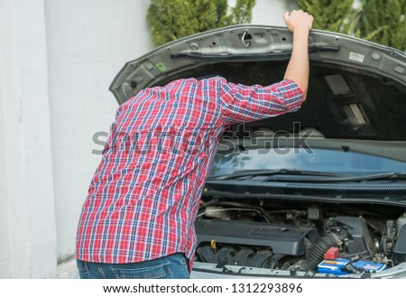 The young man stressed that there was a problem with his broken car and he was thinking of how to fix his car. #1312293896