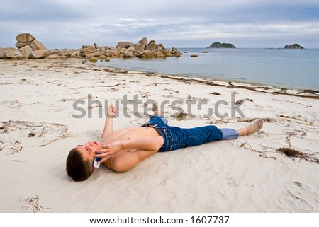 The young man talks on mobile on a deserted beach.