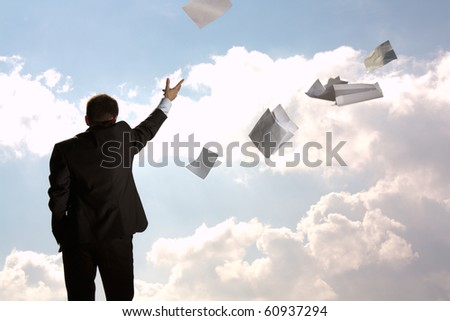 The young man, the businessman, in a dark business suit throws a pile of documents upwards, aside. The beginning of new life.