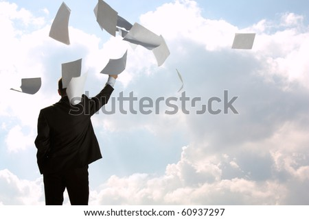 The young man, the businessman, in a dark business suit throws a pile of documents upwards, for a back. The beginning of new life.