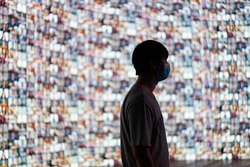 The young man wear masks stood to prepare for the event of the large LED screen, which was projecting a large number of attendees through conference program. selective focus