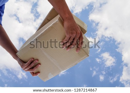 The young man who inspects the goods in the shipping company is checking the parcel and calculating the shipping cost before delivering it to the customer. Audit concept for accuracy before delivery Stock foto ©