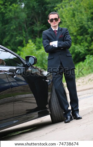 The young man with black glasses and suit stand near to expensive car