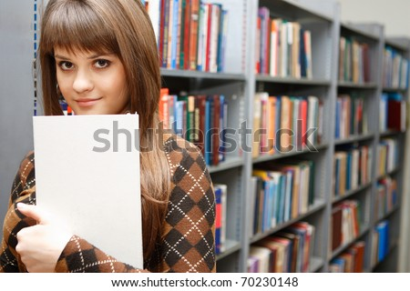 The young nice student reads and considers books on regiments in the big library, smiling in the chamber