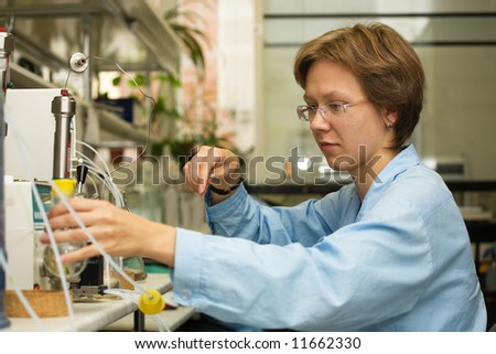 The young nice woman-scientist work with syringe on a background scientific instruments