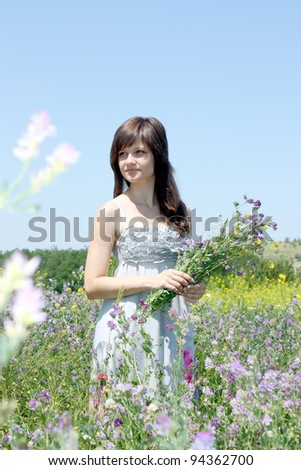 The young pretty girl collects a flowers