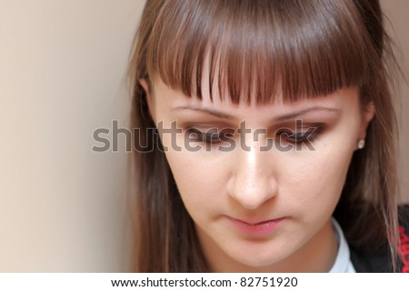The young serious woman looks down indoor