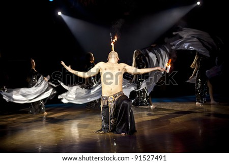The young sexual fakir man fire eater actor   eating fire dangerous fiery fascinating performance in circus at night  and breathing fire blowing fire from his mouth and wonderful bellydancers