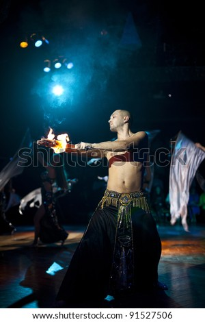 The young sexual fakir man fire eater actor   eating fire dangerous fiery fascinating performance in circus at night  and breathing fire and beauty arabic bellydancers with shawl