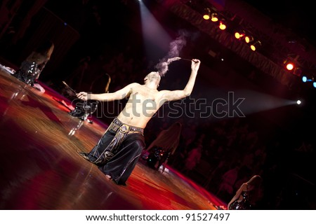 The young sexual fakir man fire eater actor  eating fire dangerous fiery fascinating performance in circus at night  and breathing fire blowing fire from his mouth