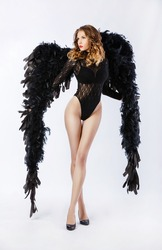 the young sexy woman in underwear with wings in an image of an angel (demon)