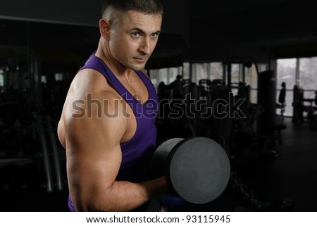 The young sportsman with a well-muscled body in a gym against a dark background