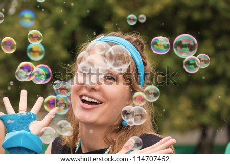 The young woman among soap bubbles