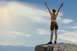 The young woman at the top of the mountain raised her hands up on blue sky background. The woman climbed to the top and enjoyed her success. Back view.