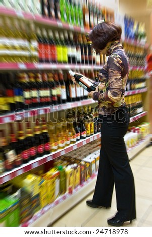 The young woman chooses wine in a supermarket