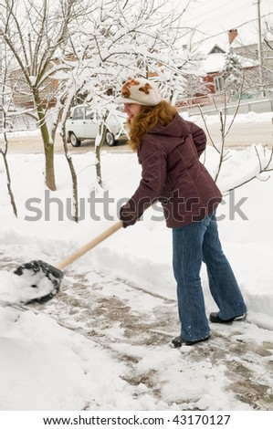 The young woman cleans snow from sidewalk.