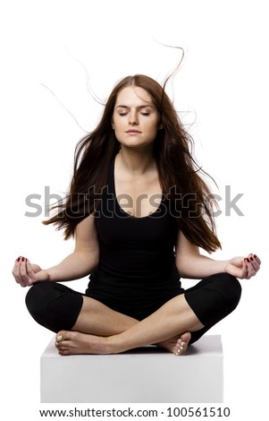 The young woman dressed in black sitting cross-legged, eyes closed and relax. The wind blows on her hair.
