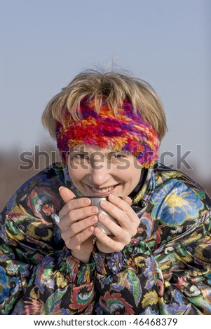 The young woman drinks a hot drink from a cup outdoor