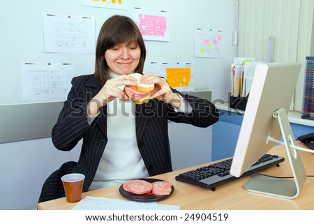 The young woman has breakfast a sandwich with sausage on work