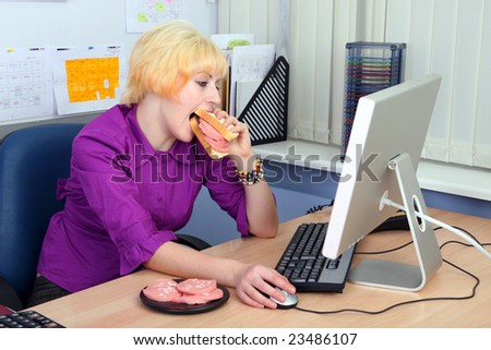 The young woman has breakfast at work
