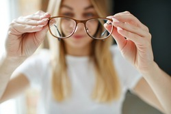 The young woman has poor eyesight. Girl holds glasses for sight in her hands.