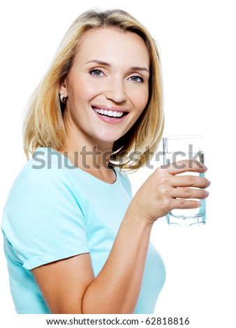 The young woman holds a glass with water on a white background