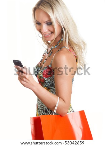 The young woman in elegant clothes looks at a mobile phone
