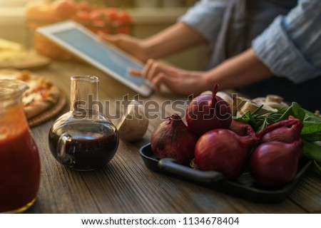 The young woman looking recipe in a tablet computer in kitchen. Healthy food. Healthy lifestyle. Cooking at home. Cooking according to recipe on tablet screen. Technology concept. Toned image.